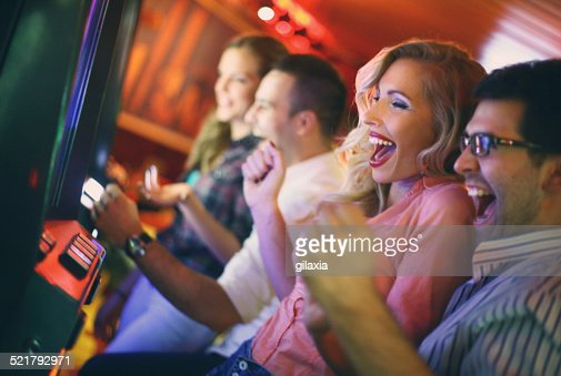 Group of people playing slots in casino.