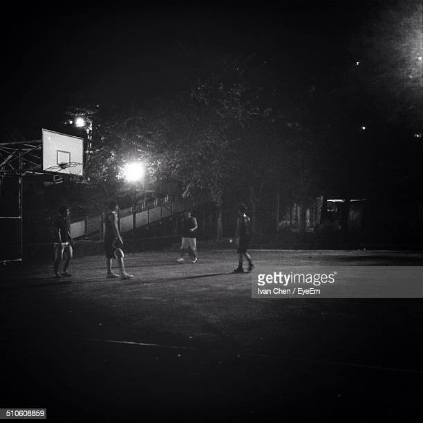 Group of people practicing basketball at night