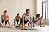 Group of diverse young sporty people practicing yoga lesson, doing Push ups or press ups pose, phalankasana, Plank exercise, working out, indoor full length, mixed race students training at sport club