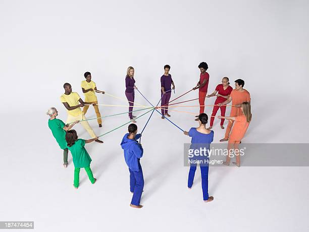 Group of people pulling connected color ropes