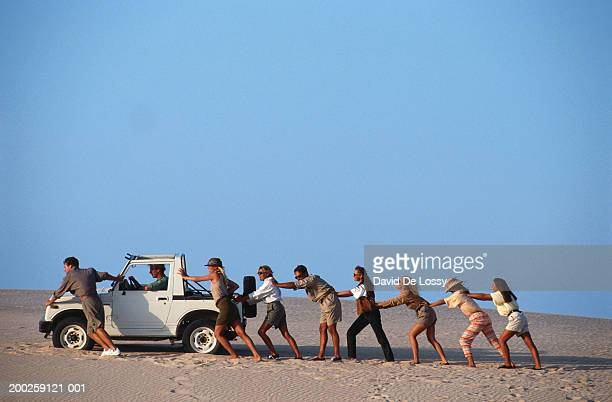 Group of people pushing off road vehicle in desert