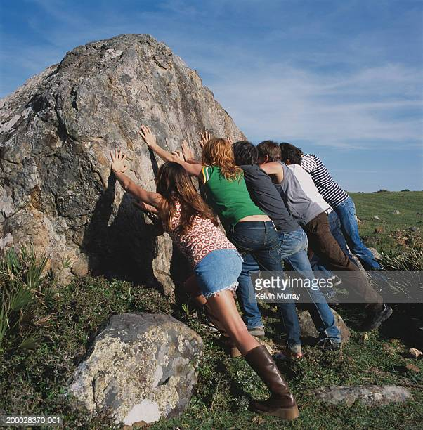 Group of people pushing rock, rear view
