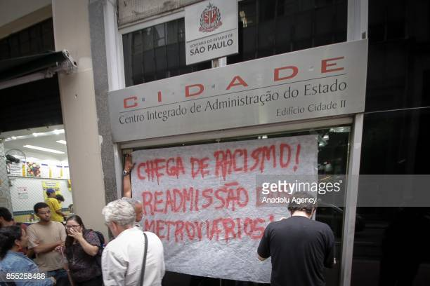 A group of people put banners on a wall during a demonstration against employee layoffs and the expansion of the privatization of subway lines in...