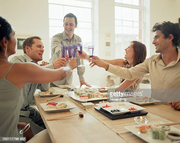 Group of people raising toast at dinner table
