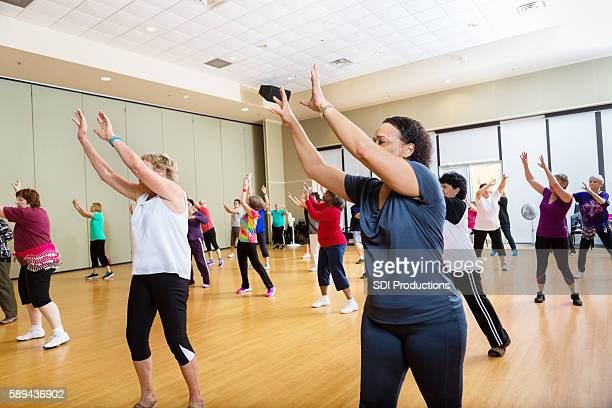 Group of people reaching up in dance class