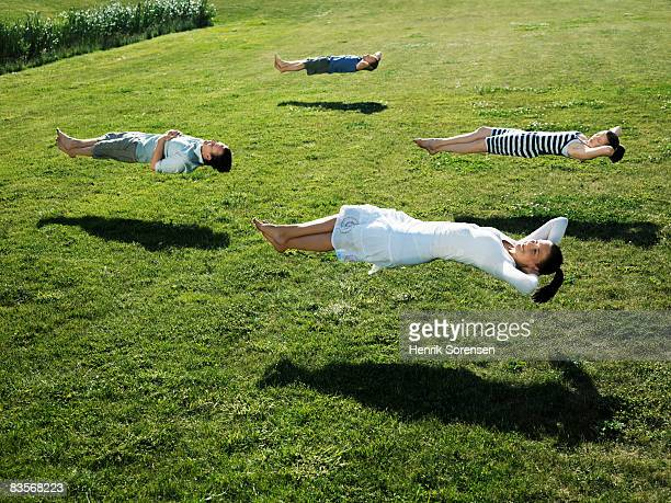 Group of people realxing floating above the grass