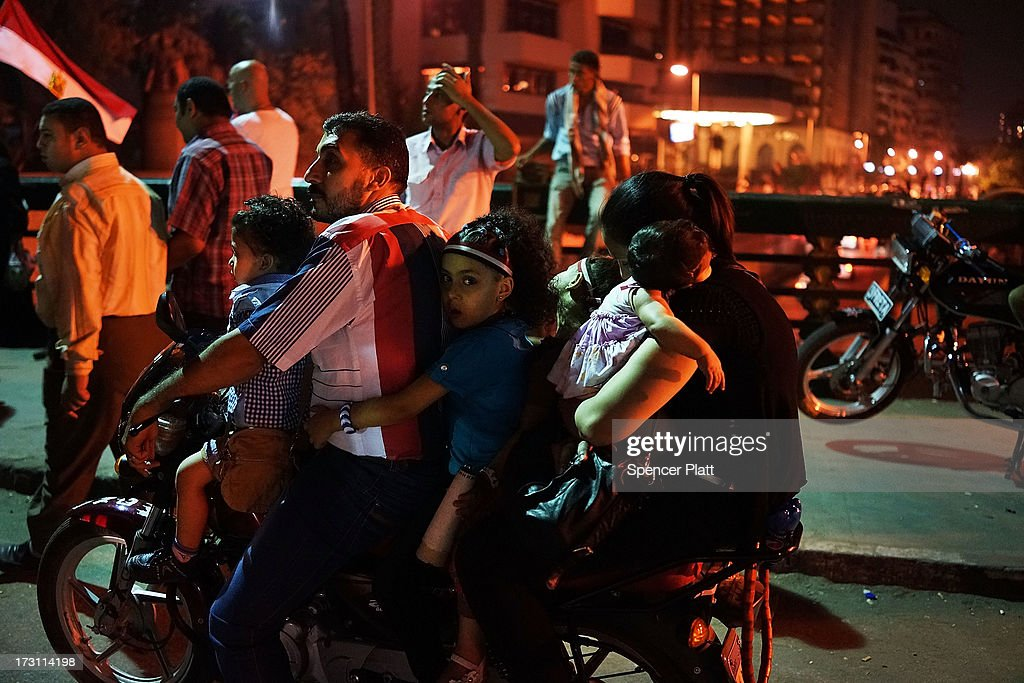 A group of people ride a motorcycle as Egyptians celebrate into the night on a bridge near Tahrir Square following a massive rally against ousted...