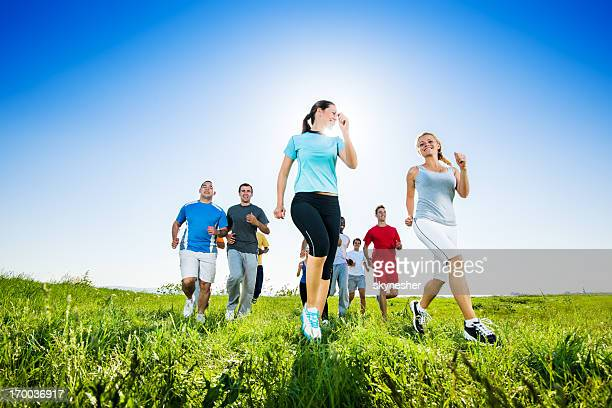Group of people running in field