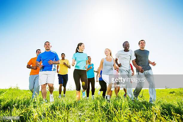 Group of people running in field.