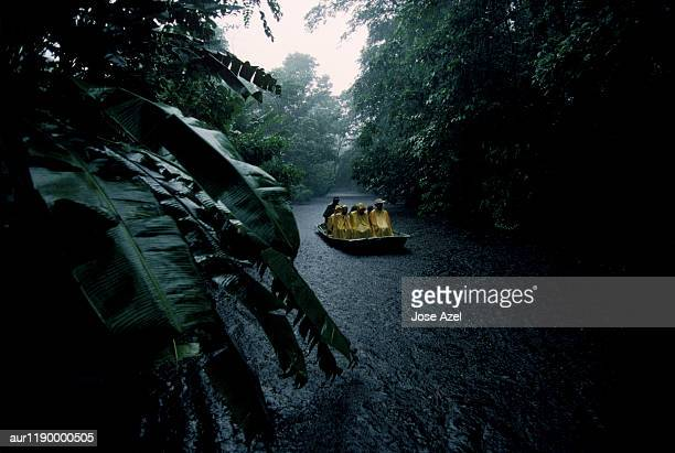 A group of people sailing in the stream amidst forest, Costa Rica, Africa.