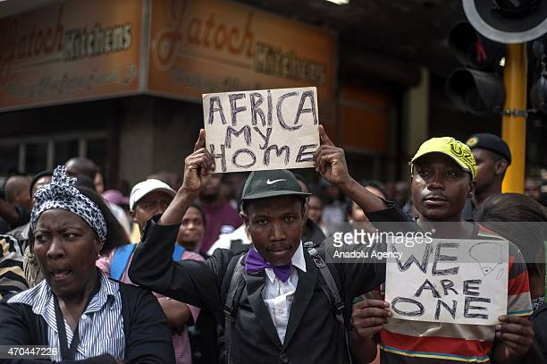 A group of people shout slogans and hold banners during an antixenophobia demonstration in front of the African National Congress Party's building in...