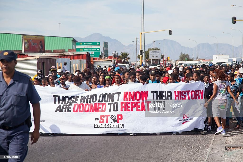 A group of people shout slogans and hold banners during an antixenophobia demonstration in Khayelitsha region of Cape Town South Africa on April 27...