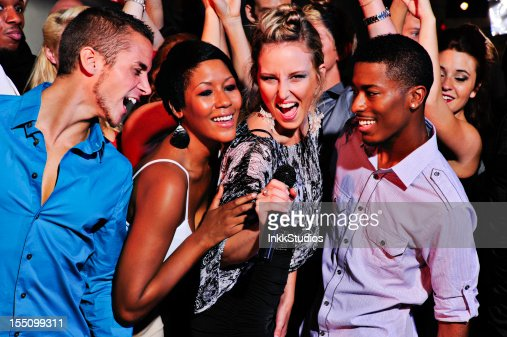 Group of people singing in a Nightclub : Stock Photo