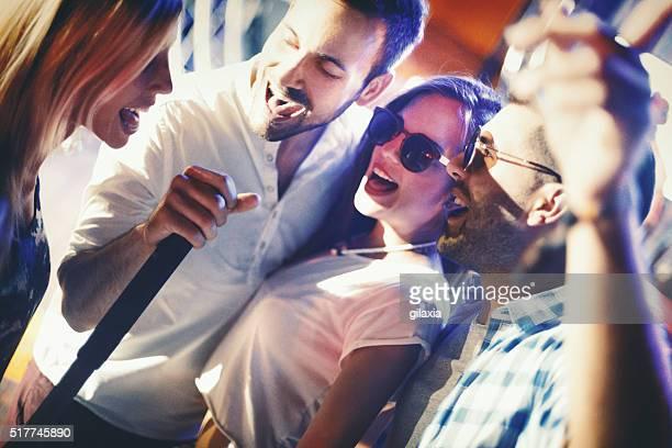 Gruppe von Menschen karaoke singen.