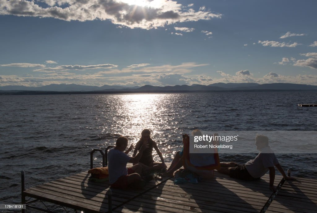 A group of people sit on a dock in the late afternoon August 3, 2013 along the shore of Lake Champlain in Charlotte, Vermont. The Adirondack Mountains and New York state lie across the lake.