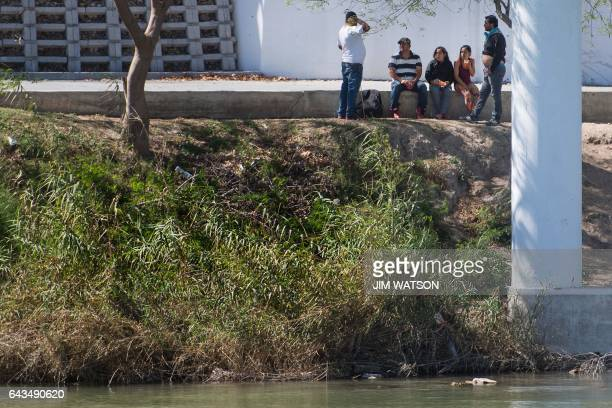A group of people sit under a bridge on the banks of the Rio Grande river on the Mexico side as seen from Eagle Pass Texas on the US/Mexico border on...