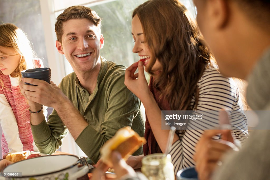 A group of people sitting at a table, smiling, eating, drinking and chatting. : Stock Photo