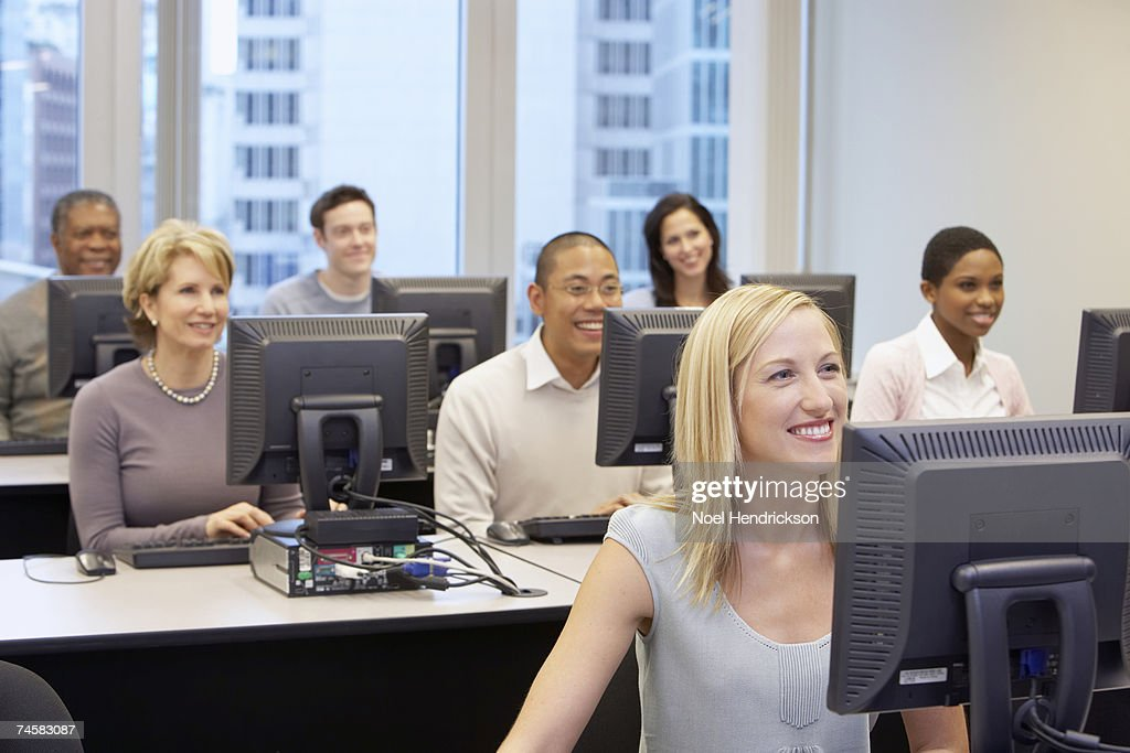 Group of people sitting at computers in office, front view : Stock Photo