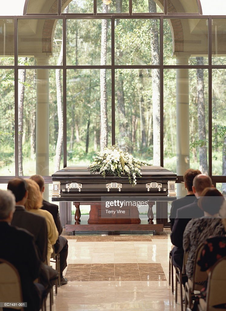 Group of people sitting at funeral, casket with flowers in front : Stock Photo