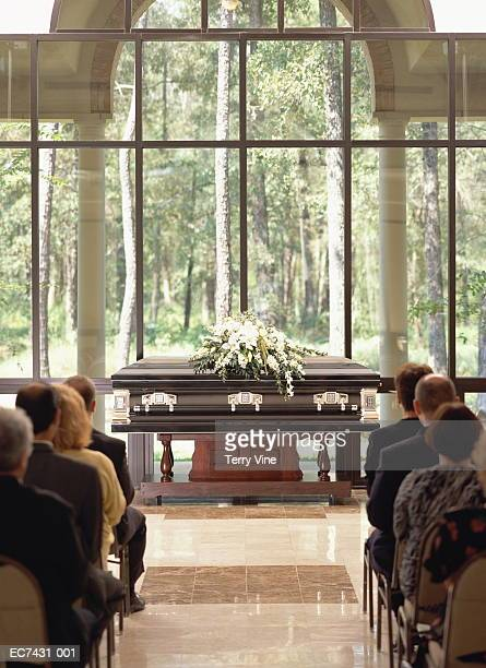 Group of people sitting at funeral, casket with flowers in front