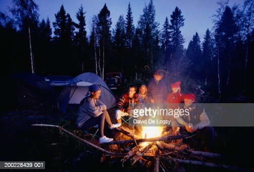 Group of people sitting by campfire : Stock Photo
