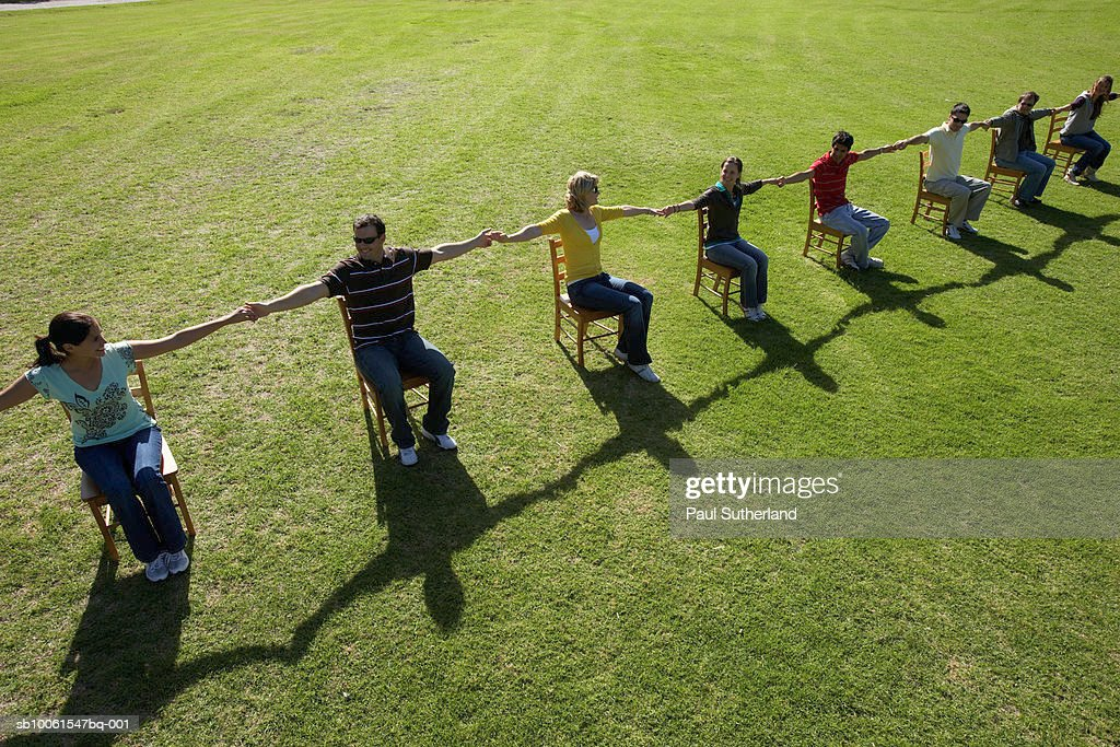 Group of people sitting on chairs in park, holding hands, high angle view