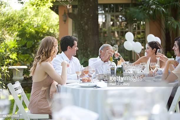 Gruppe von Menschen, die am Tisch sitzen im Freien sprechen und Lächeln