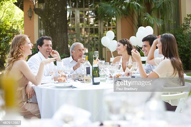 Group of people sitting outdoors at table talking and smiling