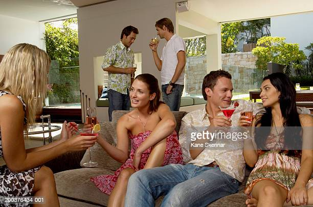 Group of people socializing indoors, holding drinks