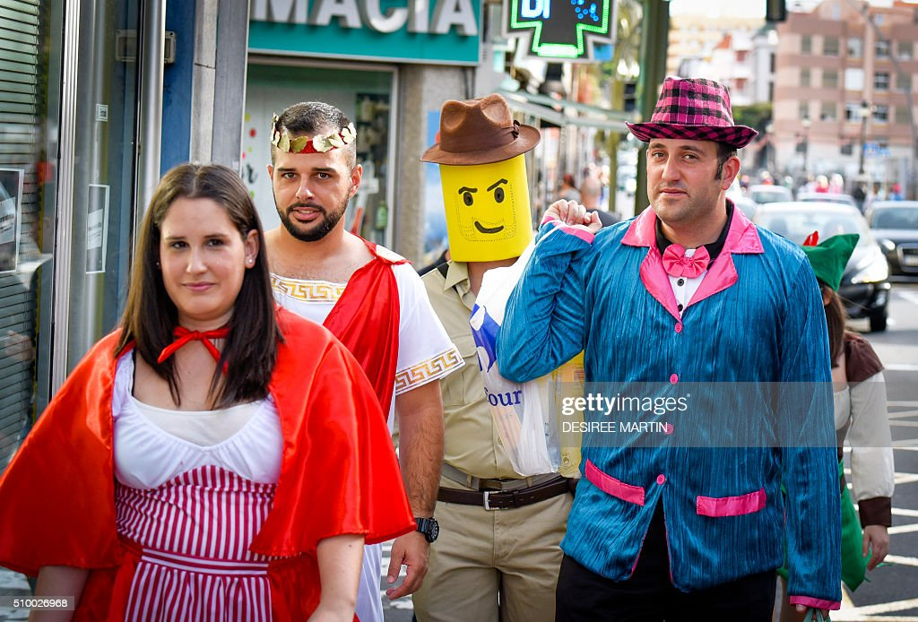 A group of people sport their costumes as they participate in a street carnival in Santa Cruz de Tenerife on the Spanish Canary island of Tenerife on February 13, 2016. The over a month long carnival sees orchestras playing Caribbean and Brazilian rhythms throughout the festivities that range from elections for the Carnival Queen, children and adult murgas (satirical street bands), comparsas (dance groups) to performances on the streets. / AFP / DESIREE MARTIN