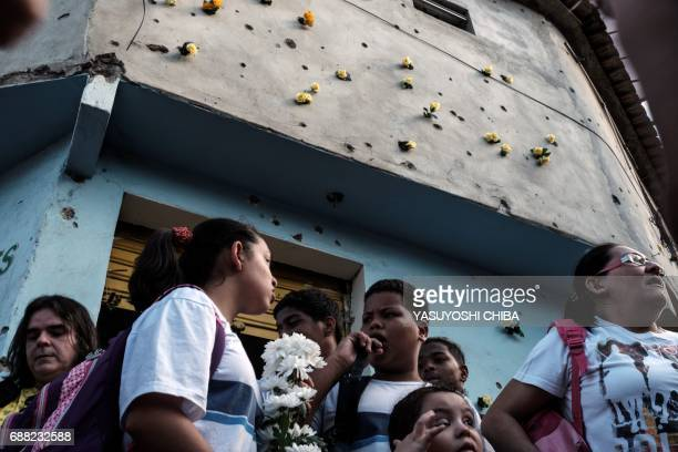 A group of people stand below a bulletriddled wall with artificial flowers inserted in the bullet holes during a demonstration against violence...