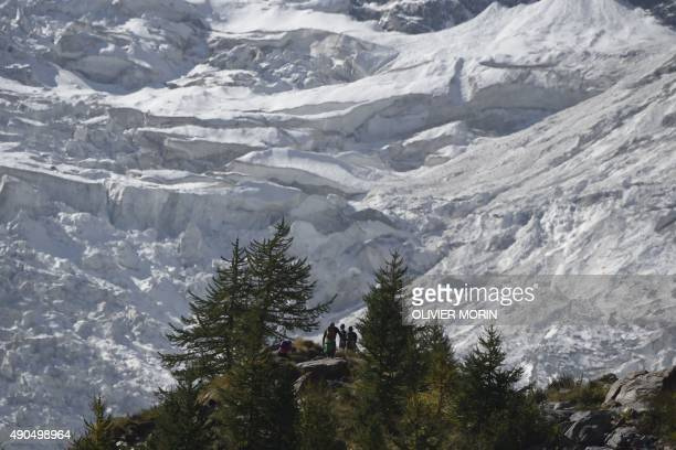 A group of people standing along the Belvedere glacier look at one of the three glaciers of the Monte Rosa on September 26 2015 The Belvedere Glacier...
