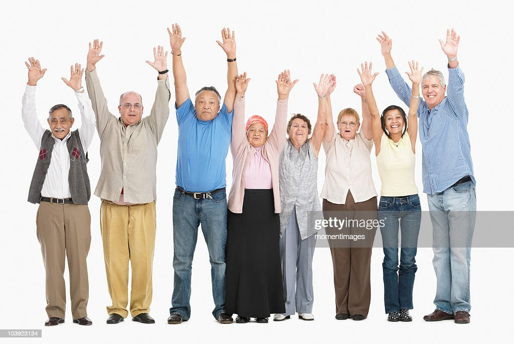 A group of people standing in a row raising their arms : Stock Photo
