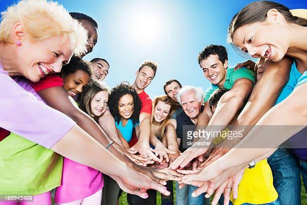 Groupe de personnes debout en cercle contre le ciel bleu.