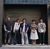 Group of people standing in front of garage door, portrait