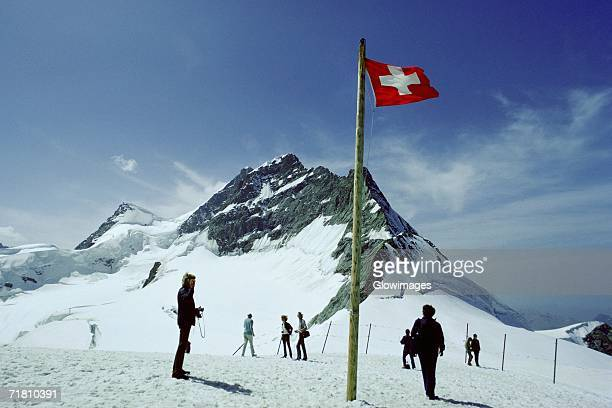Group of people standing near the Swiss Flag, Jungfrau, Switzerland