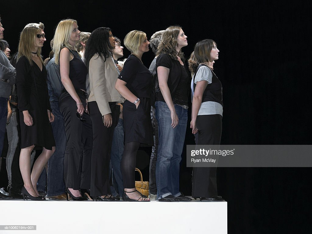 Group of people standing on catwalk : Stock Photo