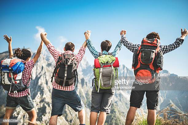 group of people standing on the mountain with arm raised