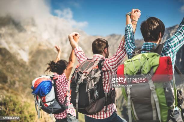 Grupo de personas de pie de la montaña con brazos elevado