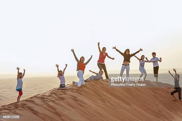 Group of people standing on top of desert dune with arms raised in air