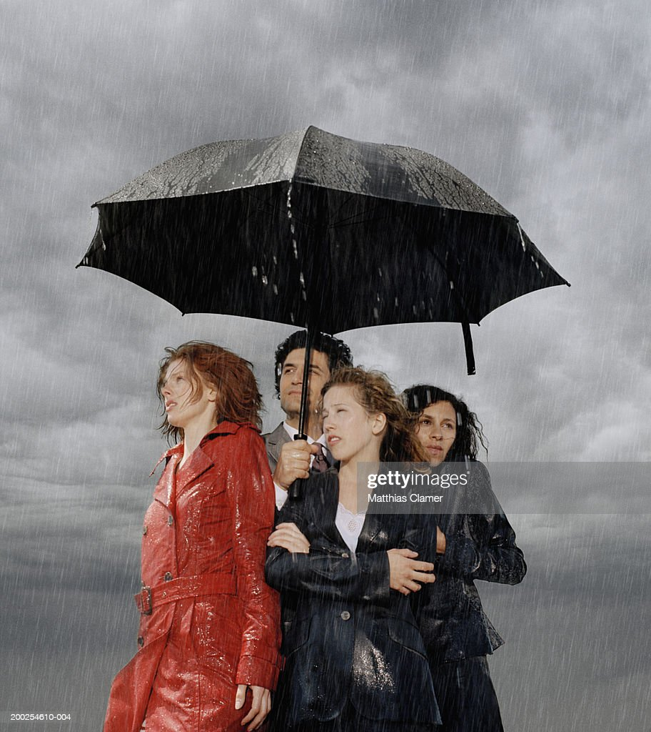 Group of people standing under umbrella in rain : Stock Photo