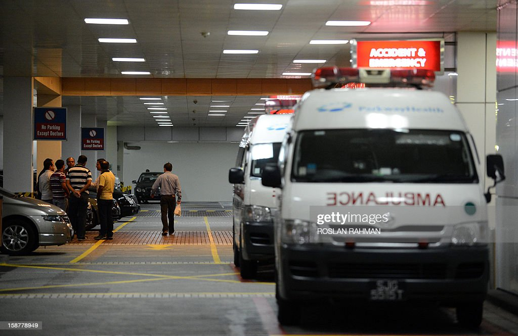 A group of people stands in front of ambulances outside the entrance of the Mount Elizabeth hospital in Singapore on early December 29, 2012. The medical condition of an Indian gang-rape victim has 'taken a turn for the worse' with 'signs of severe organ failure', the Singapore hospital treating her said in a statement issued late on December 28, 2012.