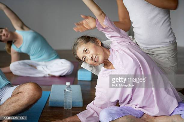 Group of people stretching in yoga class, arms raised