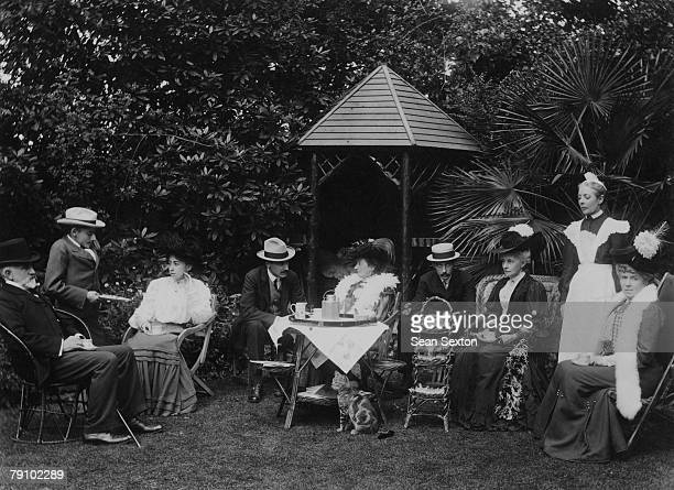 A group of people take tea in the garden circa 1905