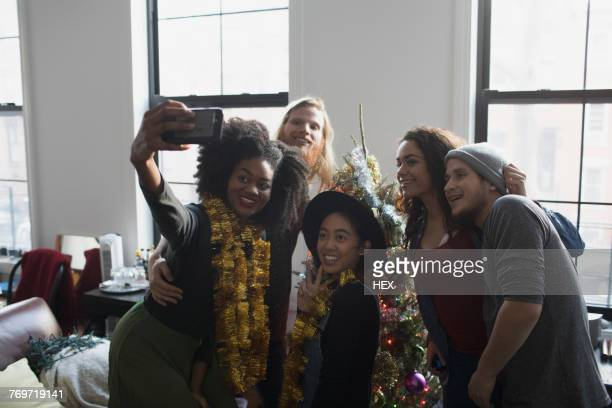 A group of people taking a photo with a Christmas tree
