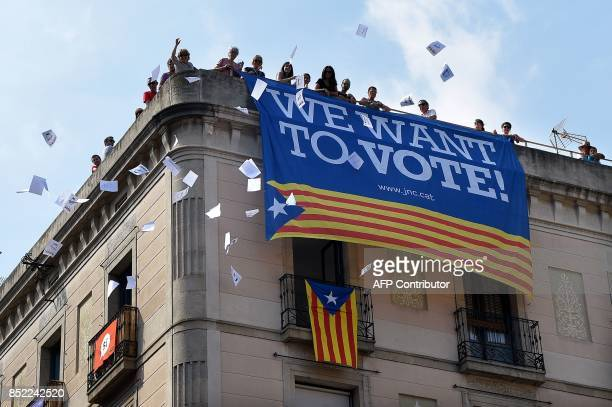 A group of people throw ballots for the October 1 referendum from a building with a banner in favour of the referendum in Sant Jaume square on...