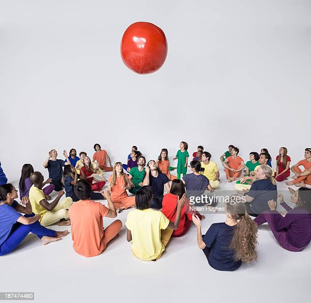 Group of people throwing a red ball in the air