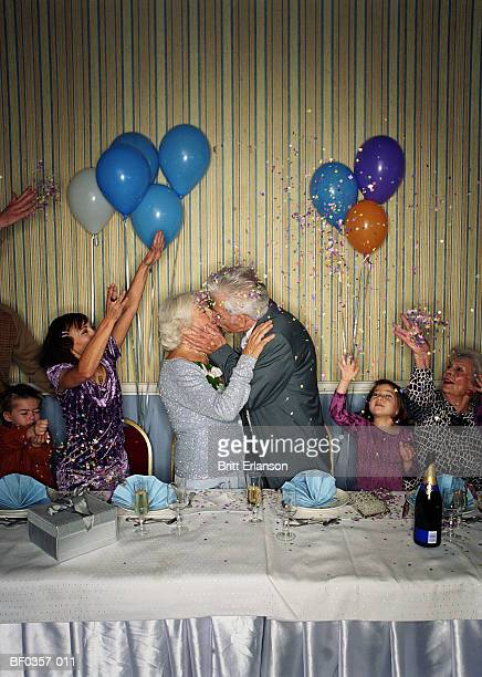 Group of people throwing confetti over elderly couple kissing