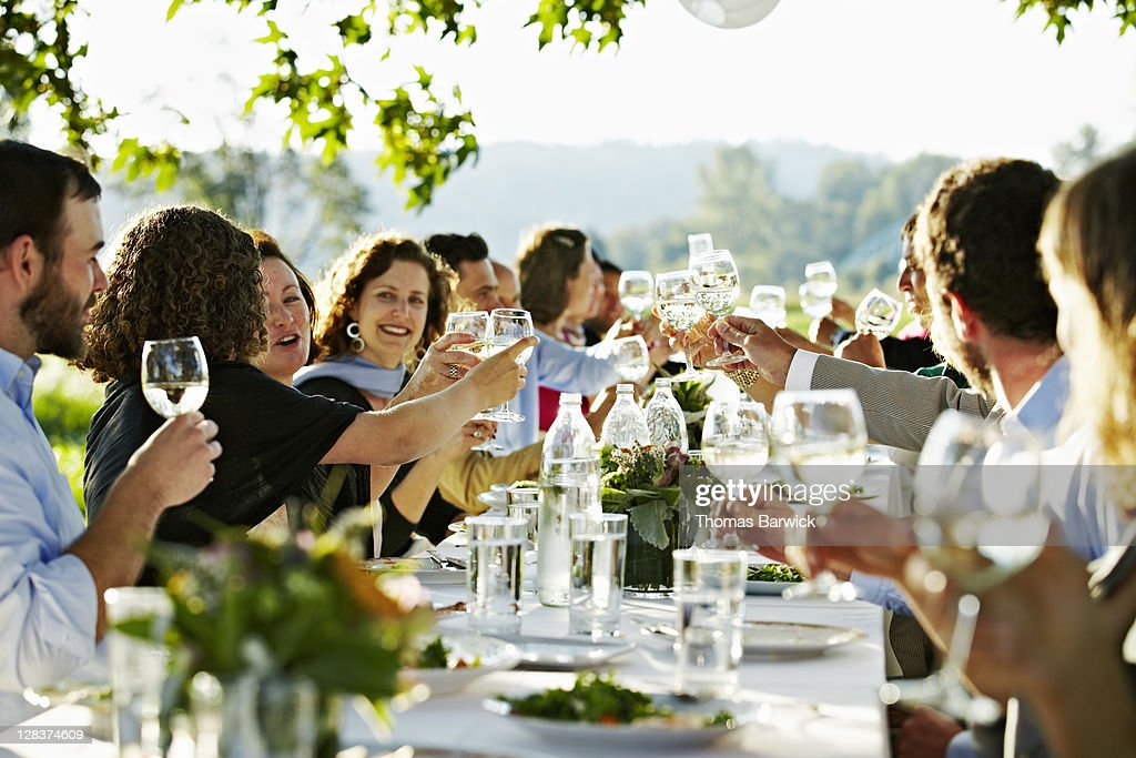 Group of people toasting at table outside in field