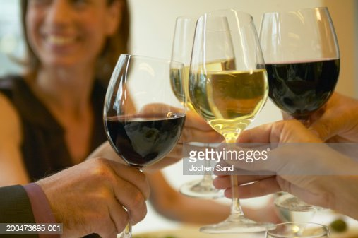 Group of people toasting wine, close-up (focus on glasses and hands) : Stock Photo